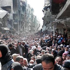 Von Krieg bedrohte Menschen in Syrien vor Ruinen