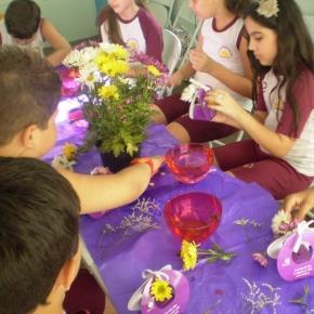 Crianças confeccionam arranjos florais.