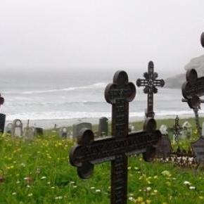 Gräber, die am Meer auf einer Wiese liegen.