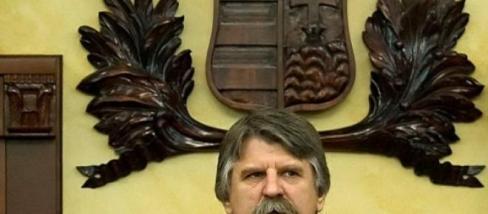 Kövér László, házmester egy címeres képpel pózol