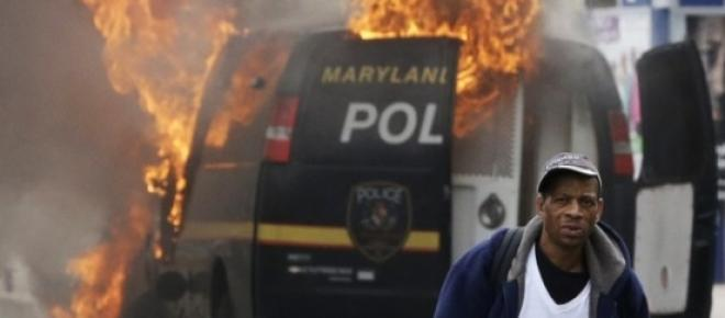 A police van in Baltimore set ablaze during protests that turned violent in the aftermath of the funeral for Freddie Gray.