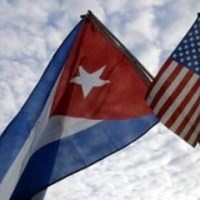 Old lady holding Cuba and US flags.
