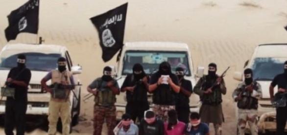 IS Kämpfer mit Geiseln in einem Propagandavideo.