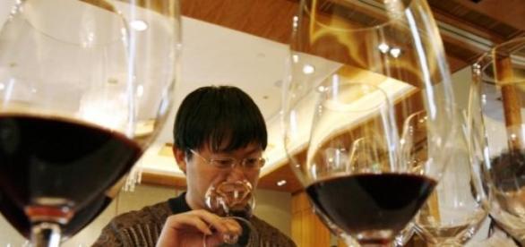 Cinese degusta un bicchiere di vino rosso