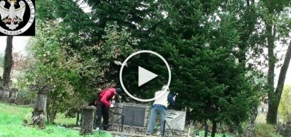Dwóch mężczyzn dewastuje pomnik UPA.