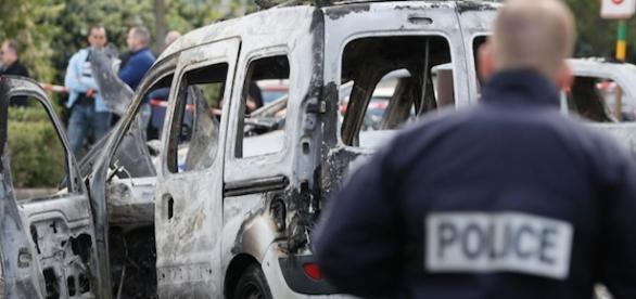 l'express.fr Un policier devant l'une des carcasses incendiées