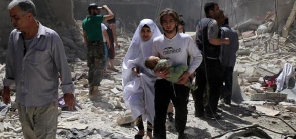 Habitantes de Aleppo caminan en medio de los escombros
