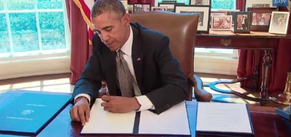 Obama signing a memorandum. YouTube (Screencap – The White House)
