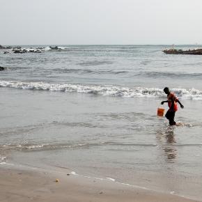 Enfant sénégalais, jouant au fot avec une balle improvisée près du port de Dakar