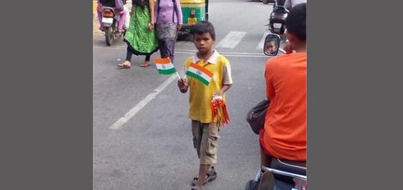 A boy sells Indian Tricolors on a busy road ahead of the country's 70th independence day on August 15, Source: Shubham Ghosh