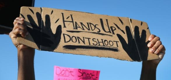 "BLM protester holding up ""hands up, don't shoot"" sign. - google images"