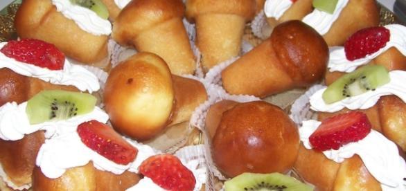 Questi sono babà in miniatura ricoperti di panna e frutta fresca.