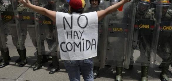 Manifestante protesta diante de policiais do governo.
