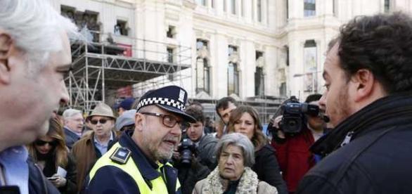 Un agente de Policía Municipal discute con los manifestantes de Hazte Oír frente al Palacio de Cibeles. OLMO CALVO