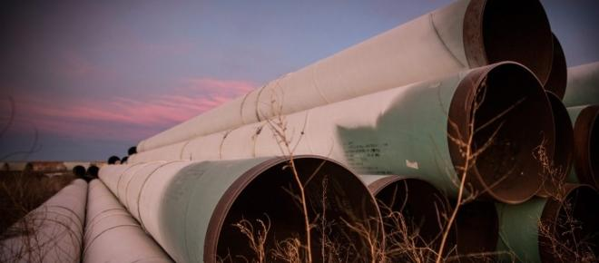 A fatigued-looking Donald Trump issues a permit to build the Keystone Pipeline