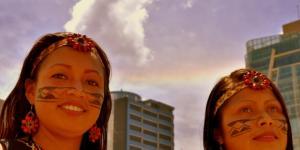 Dos chicas indígenas de la amazonía ecuatoriana posan para nuestro lente, y un arco iris de fondo pone la nota extraordinaria a esta imagen en QuitoEC