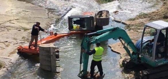 Escavatore si ribalta sul fiume Oreto a Palermo.