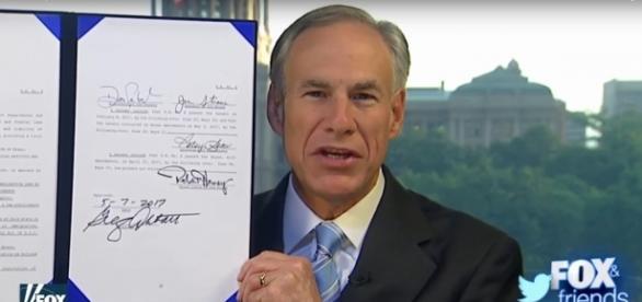 Texas Republican Gov. Greg Abbott shows signed SB4 bill Image screencap via Fox News/YouTube