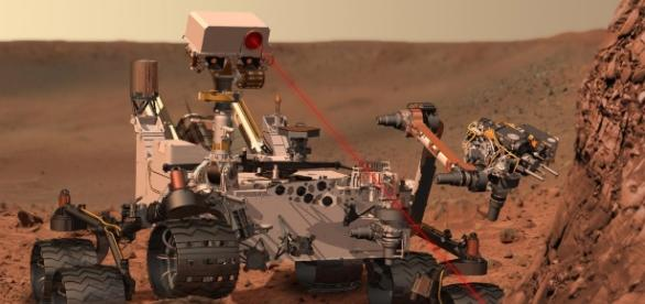 Un rendeering di Curiosity mentre punta il suo spettrometro laser sul suolo marziano