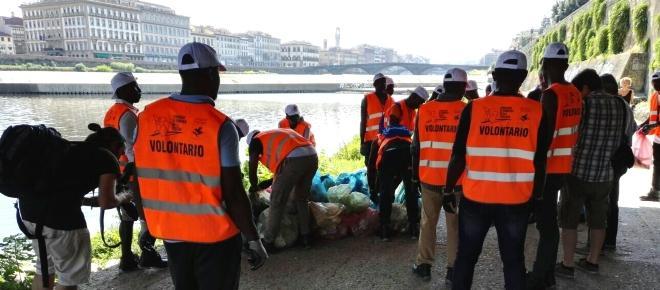 Migranti puliscono le sponde dell'Arno