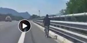 Migrante in bicicletta in autostrada